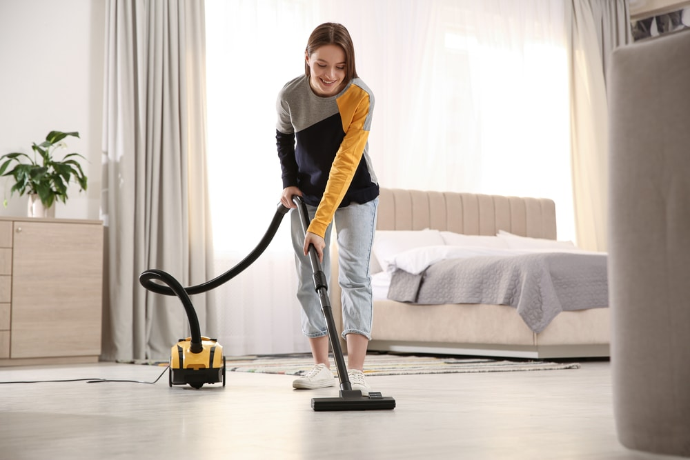 A woman vacuuming the floors of the bedroom.