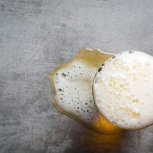 A glass of beer with its spill on the side.