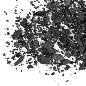 A pile of charcoal scattered on a white surface.