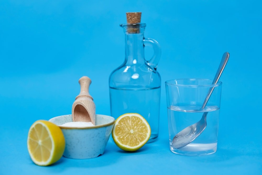 Lemon, vinegar and salt against a blue background.