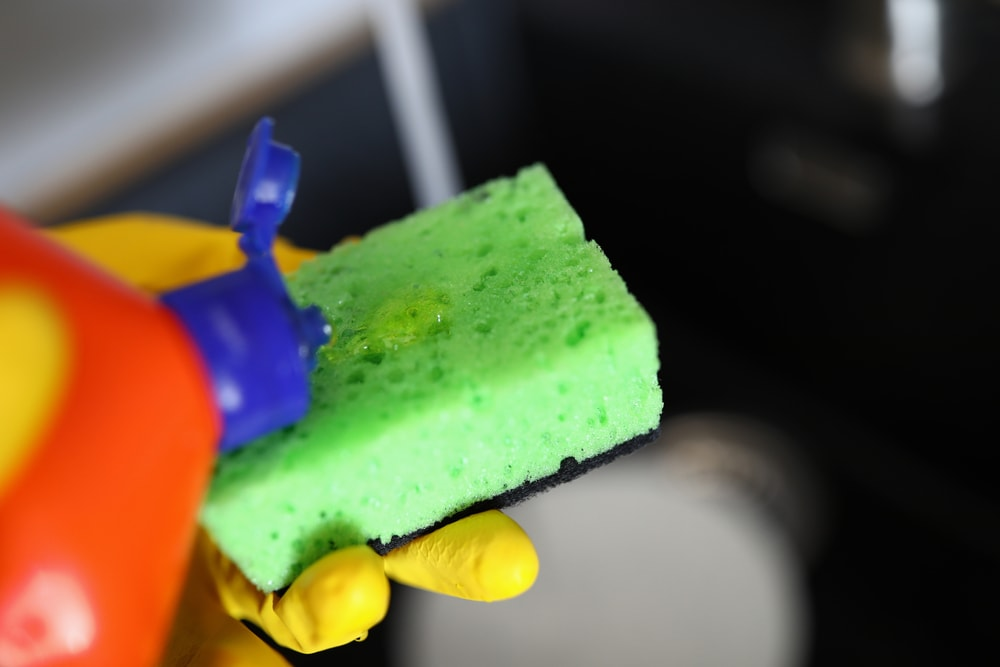 A close look at a dish detergent being poured onto a sponge.