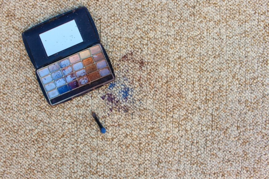 A look at an eye shadow kit that fell on the beige carpet.