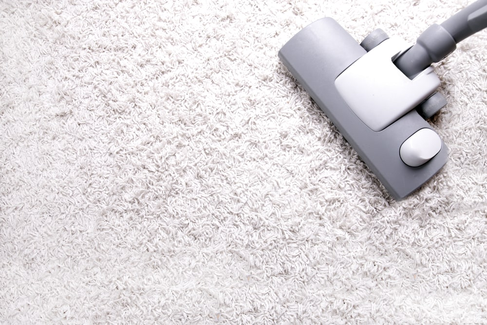 A look at a beige carpet being vacuumed.