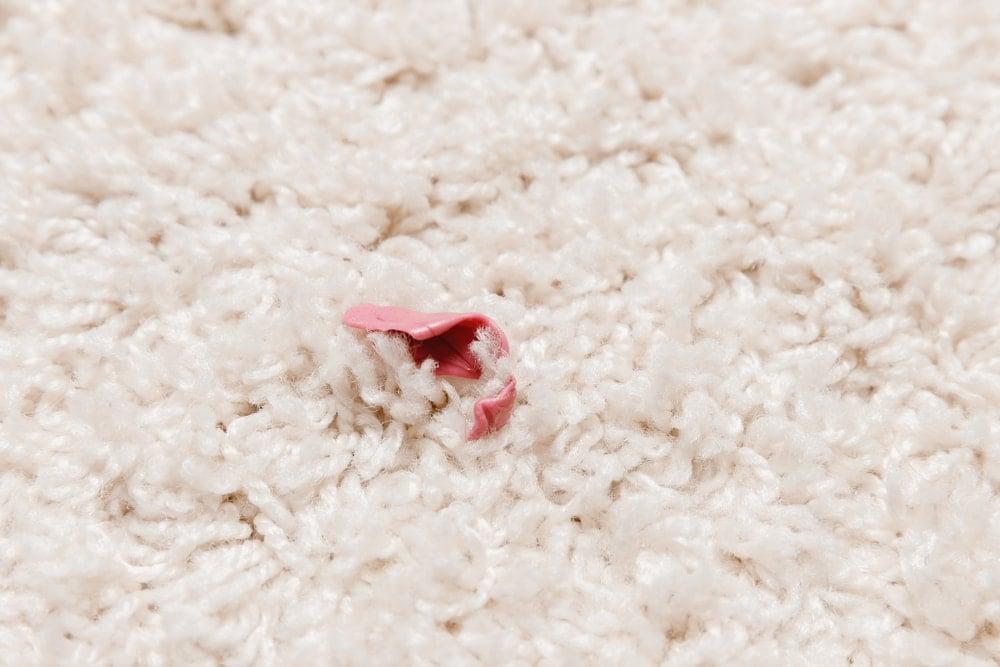 A close look at gum stuck on a beige carpet.