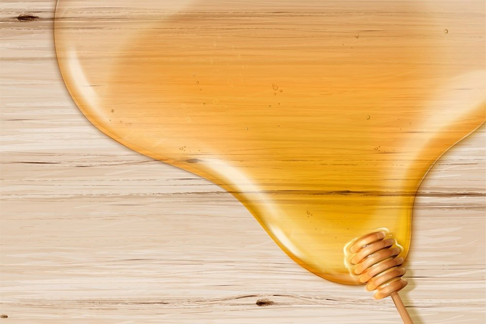 A puddle of spilled honey with a wooden dipper on a wooden surface.