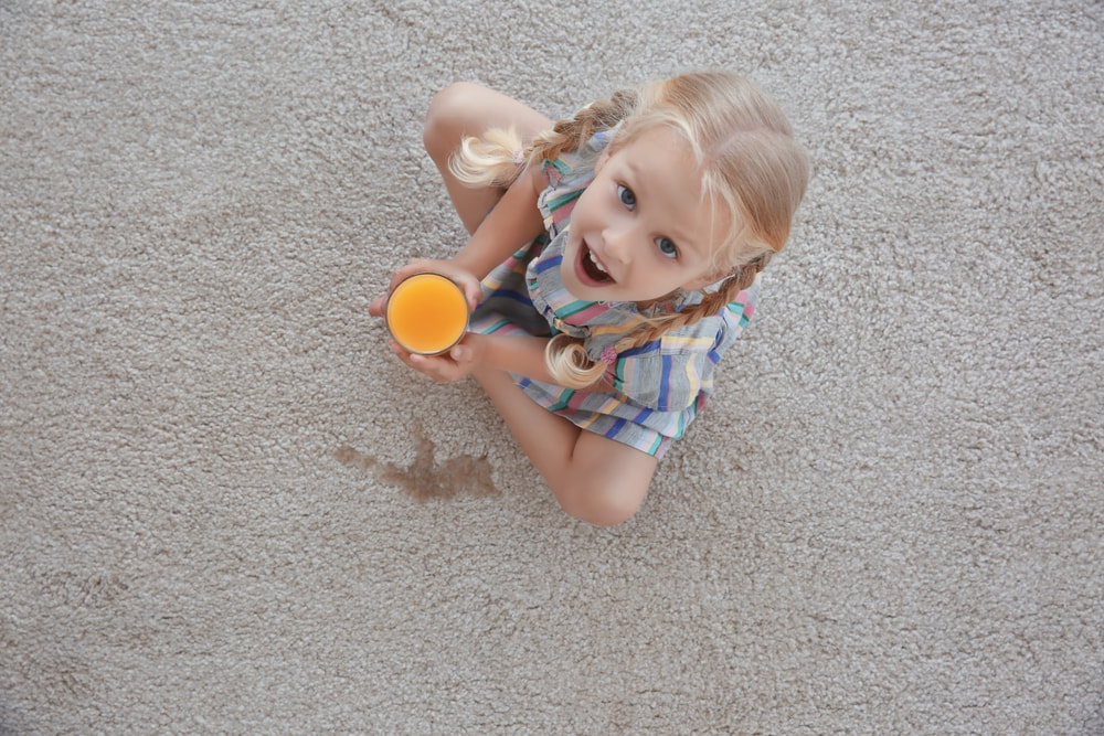 A girl accidentally spilled juice on the carpet.