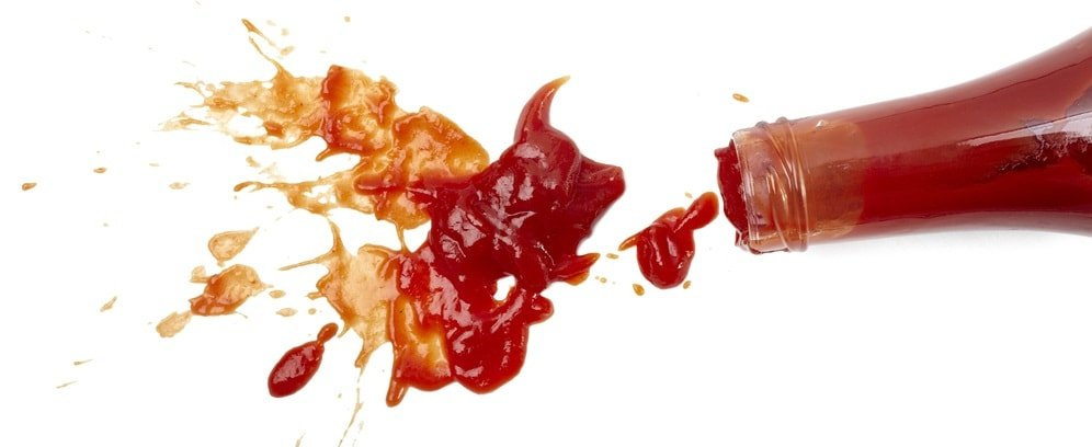 A bottle of ketchup that spilled on a white surface.