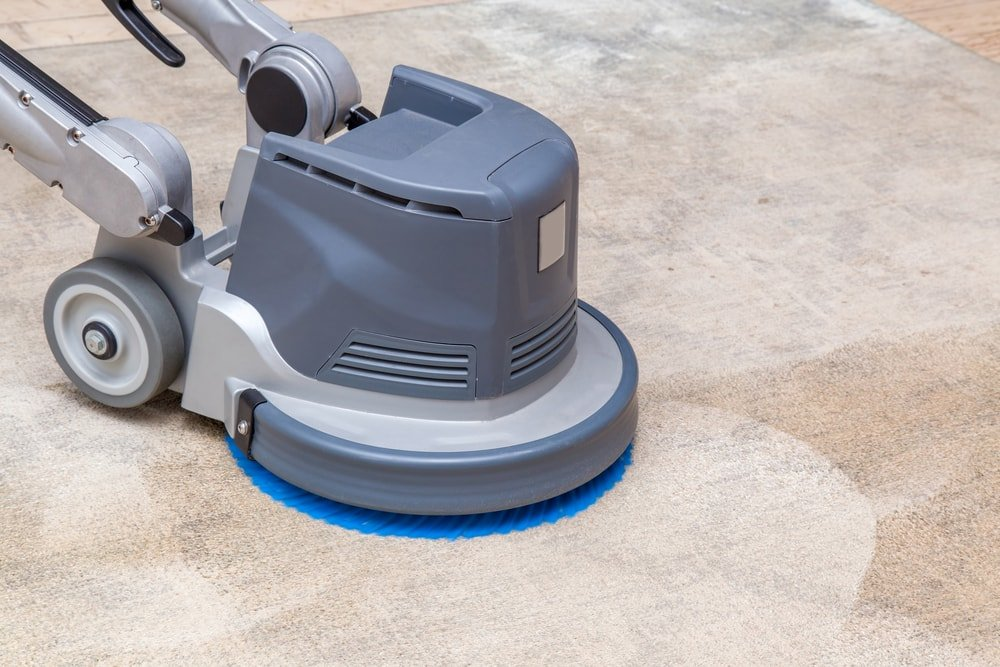 A beige carpet being cleaned with a machine.