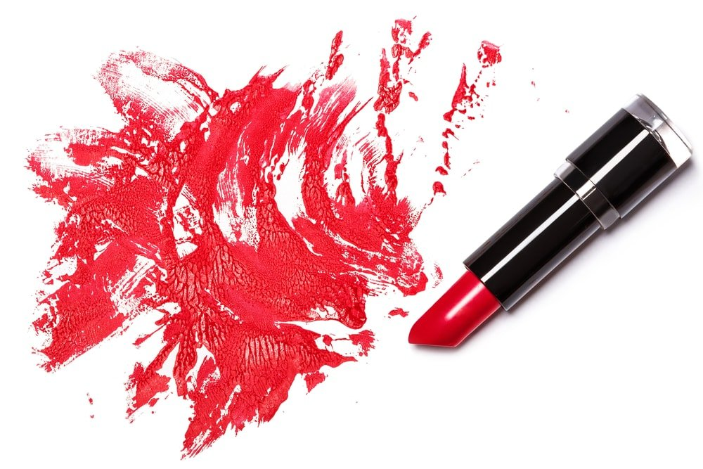 A lipstick and a red stain next to it.