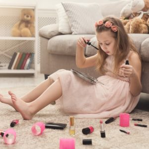 A girl playing with her mother's cosmetics on the living room carpet.