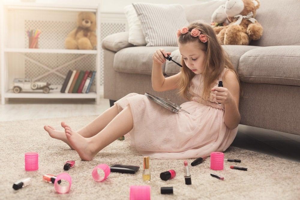 Oturma odası halısının üzerinde annesinin kozmetik ürünleri ile oynayan bir kız.