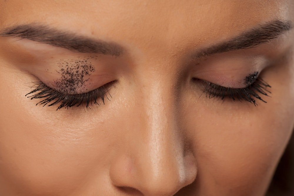 A close look at a woman with smudged mascara on her eye lids.