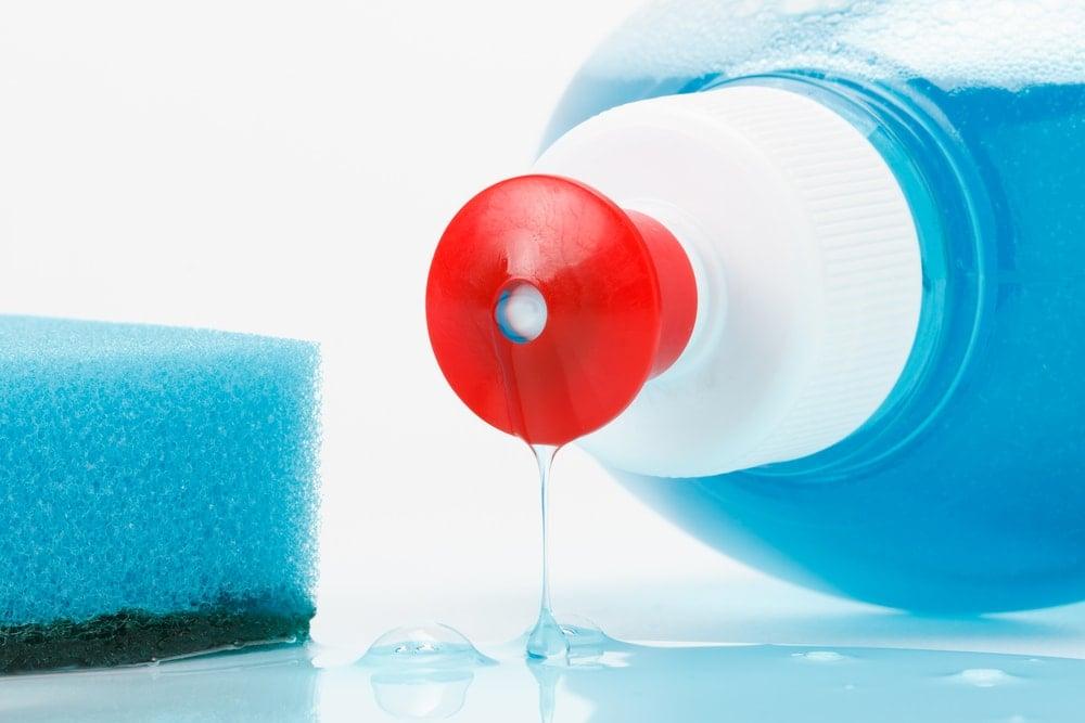 Bir süngerin yanında bulunan bir şişe bulaşık deterjanına yakından bakış.