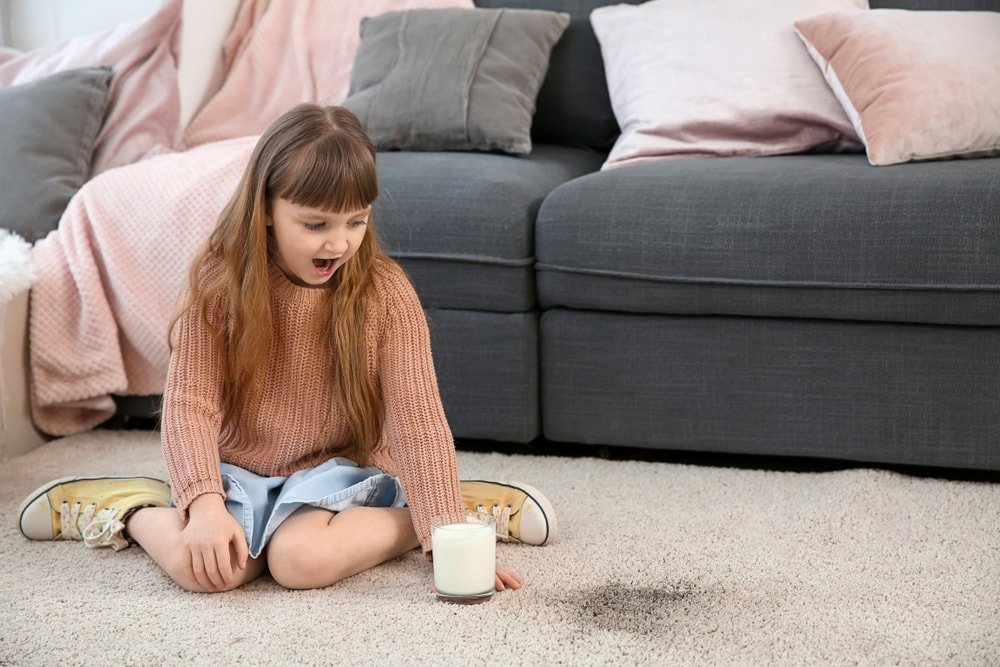 A girl accidentally stained the light beige carpet with her glass of milk.