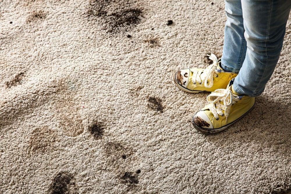 Çamurlu bir halı üzerinde çamurlu ayakkabıları olan birine yakından bakış.