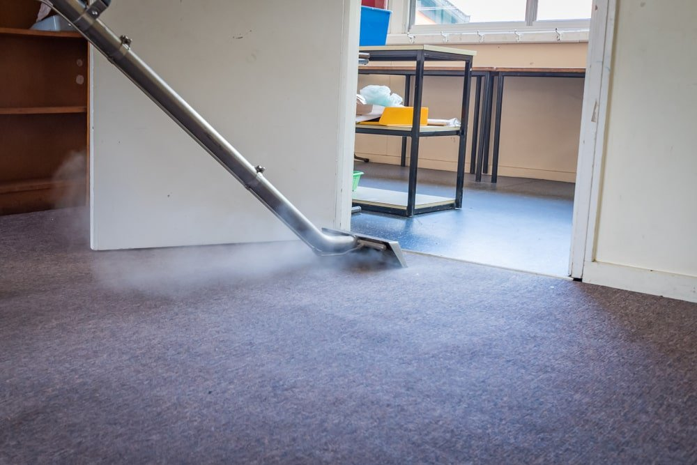 A gray carpeted-floor is being cleaned with a steam cleaner.