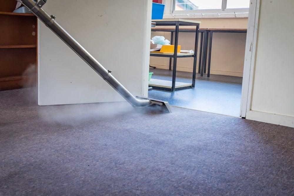Gri halı kaplı zemin buharlı temizleyici ile temizleniyor.