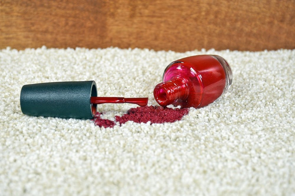 A close look at a bottle of red nail polish that spilled on the carpet.