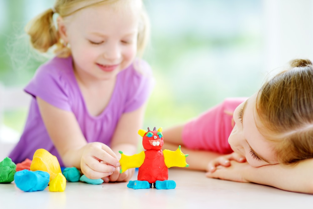 A close look at two children playing with playdough.