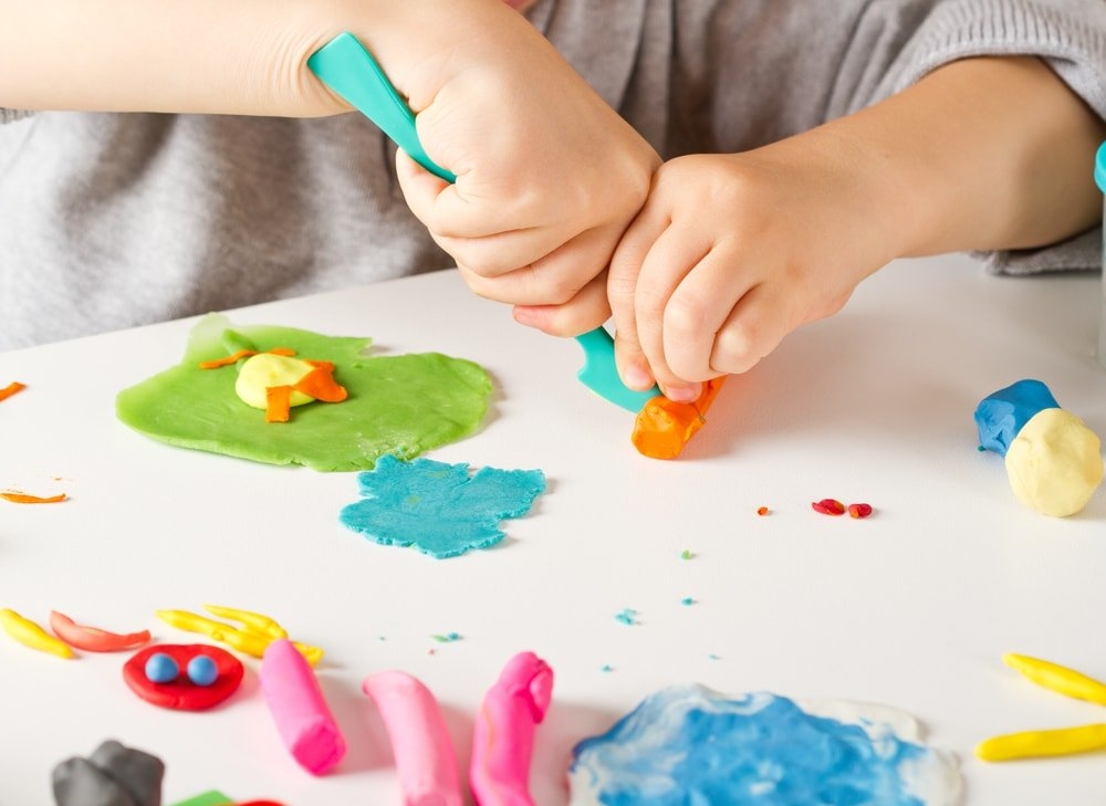 A close look at a child playing with playdough of different colors.