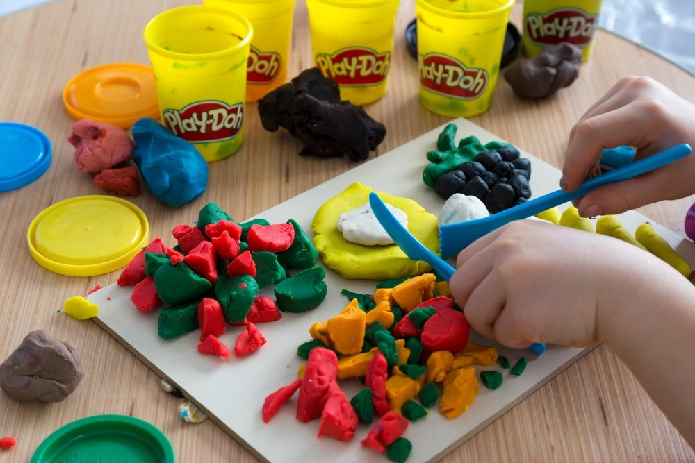 A close look at a child playing with a lot of playdough.