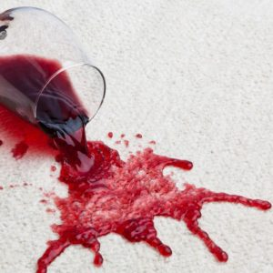 A toppled glass of red wine on a beige carpet.