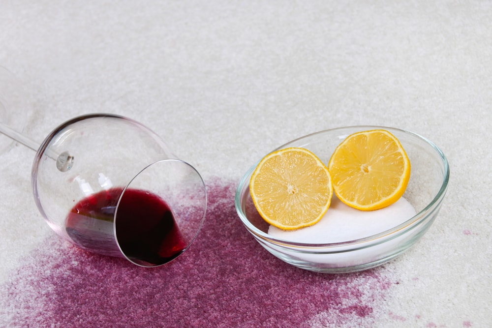 A spilled glass of red wine on the carpet beside a bowl of salt and lemon.