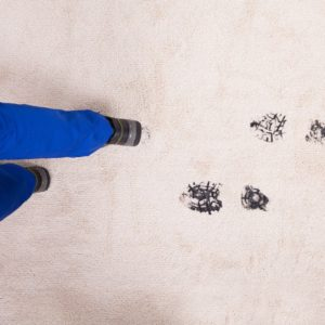 A person leaving dirty shoe prints on the beige carpet.