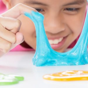 A close look at a kid playing with colorful slime.