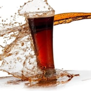 A glass of soda splashed with more soda.