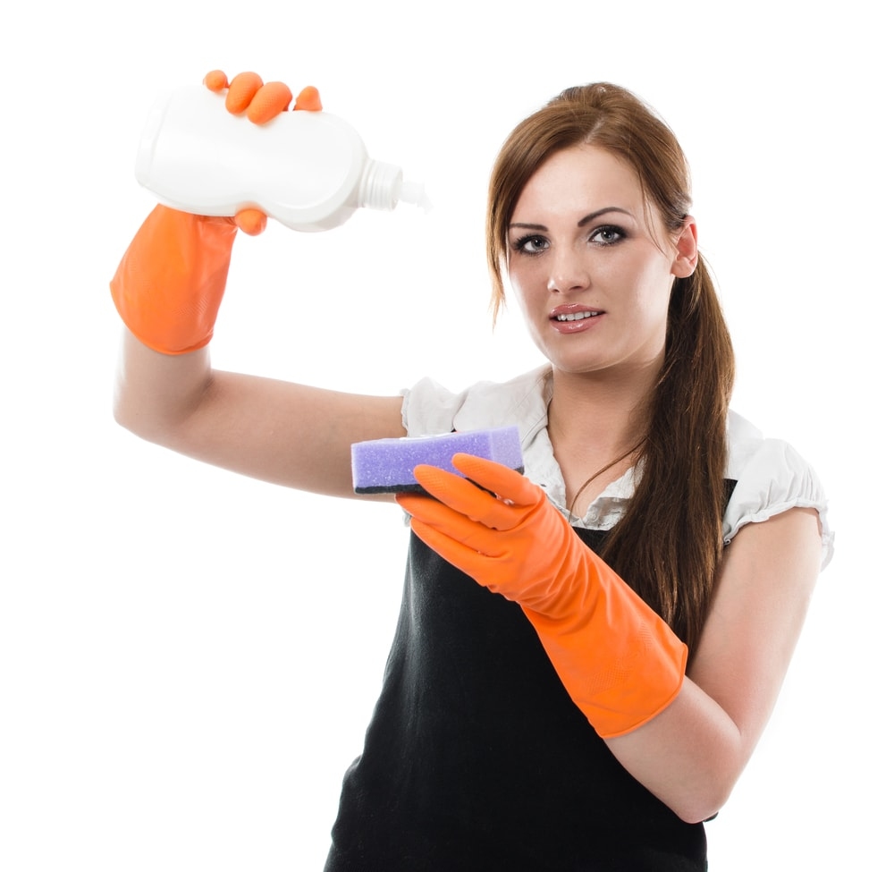A gloved woman pouring detergent onto a sponge.