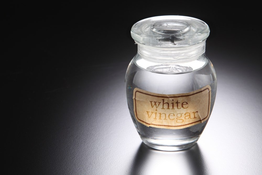 A glass jar filled with white vinegar.