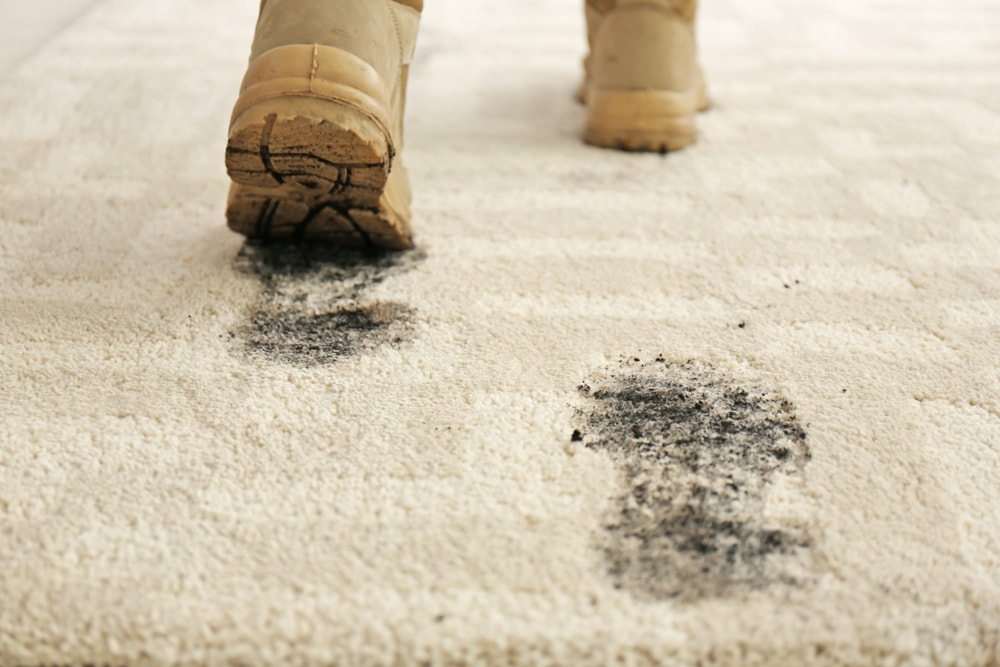 A person with dirty shoes walking on a light beige carpet.