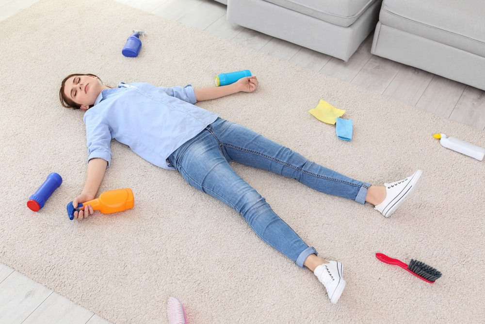 A woman lying on the carpet tired from cleaning.