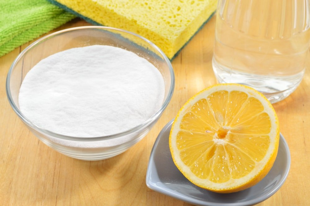 A slice of lemon and a glass bowl of salt next to cleaning materials.