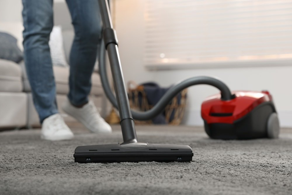 A man vacuuming the gray carpet.