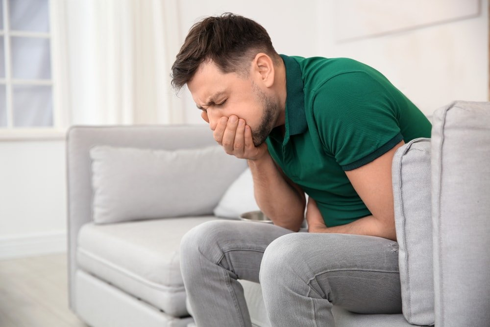 A man sitting on the couch suffering from nausea.