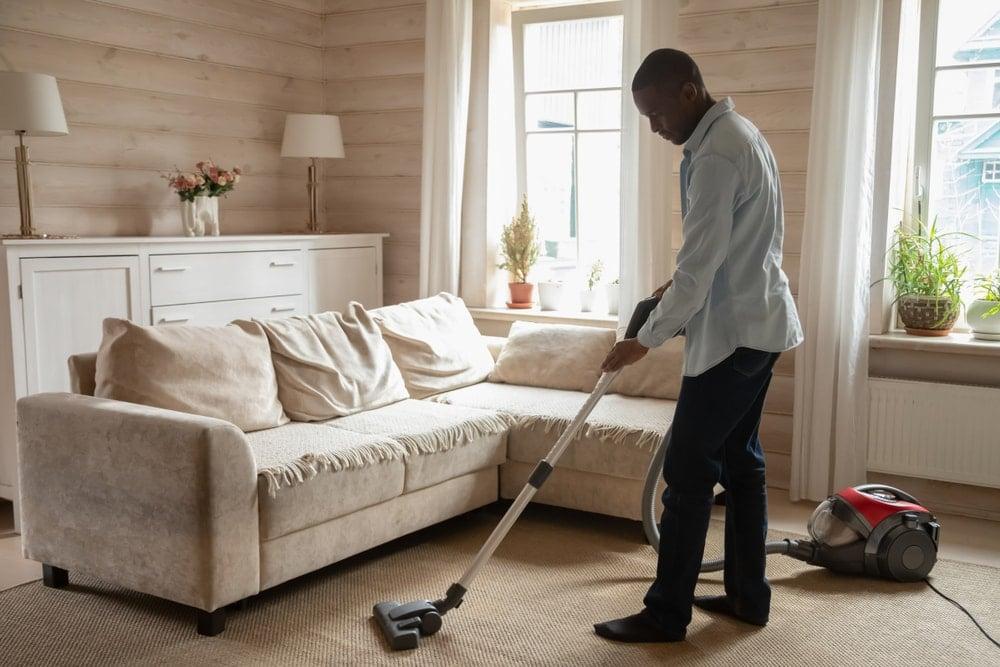 A man vacuuming the beige carpet.