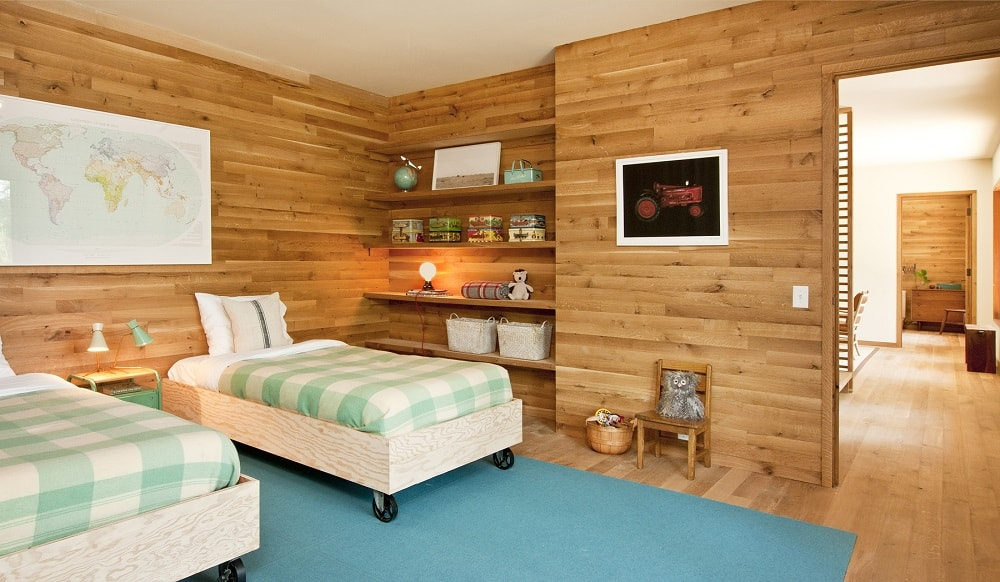 This is the bedroom with wooden walls that match the hardwood flooring. Here you can see that there are built-in shelves on the side of the bed. Image courtesy of Toptenrealestatedeals.com.