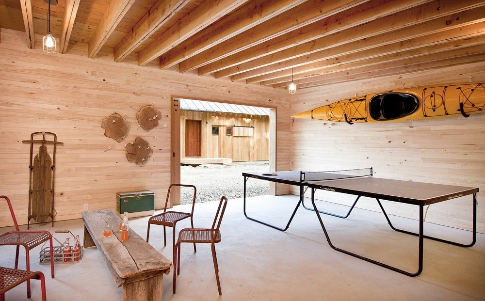 This is the detached garage that is converted into a game room. It has wooden walls that match the wooden ceiling with exposed beams. Image courtesy of Toptenrealestatedeals.com.