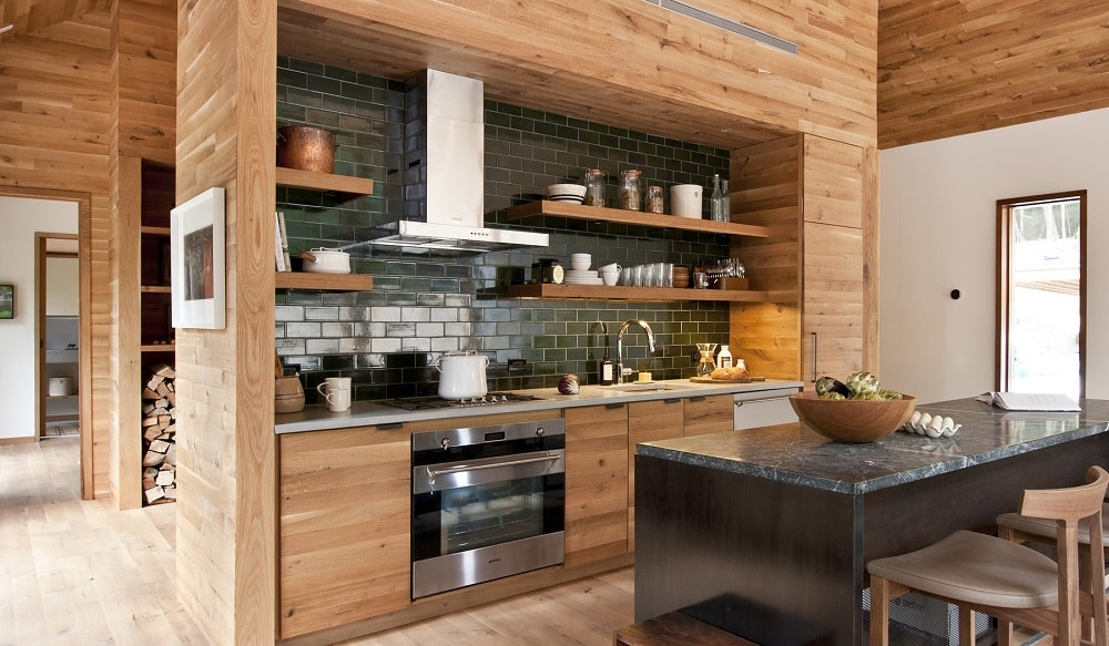 This is the kitchen that has a large black kitchen island that matches the backsplash of the cooking area. This has wooden cabinetry and shelves that match the surrounding wooden walls and hardwood flooring. Image courtesy of Toptenrealestatedeals.com.