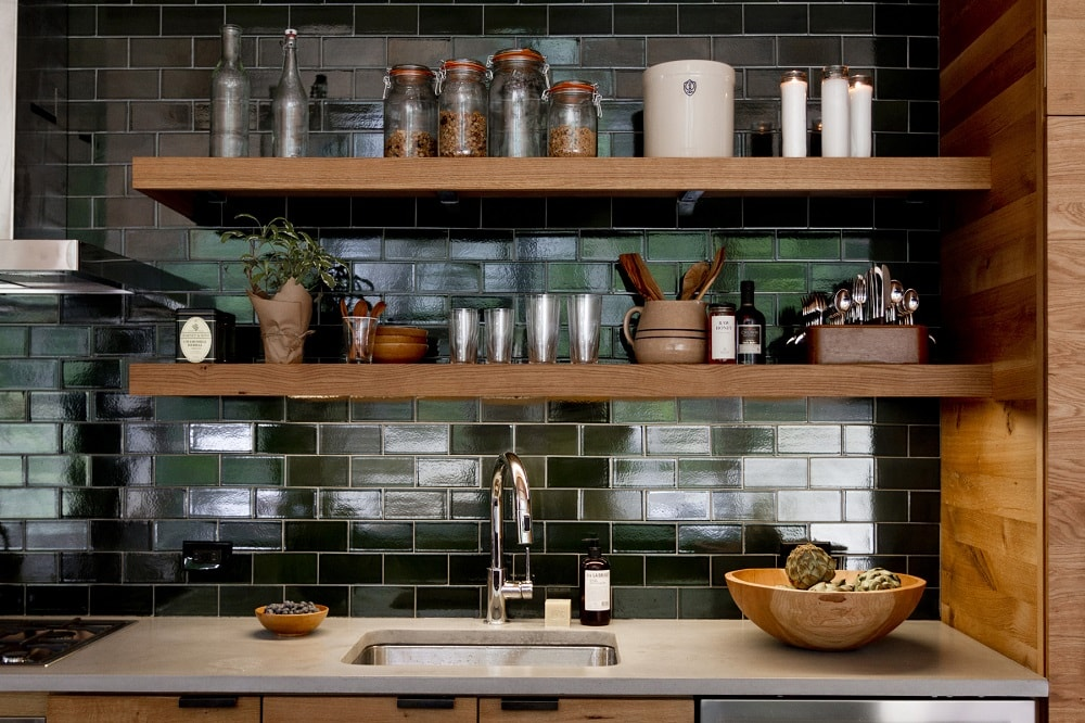 This is a closer look at the kitchen showcasing its black subway tiles on the backsplash adorned with wooden floating shelves. Image courtesy of Toptenrealestatedeals.com.