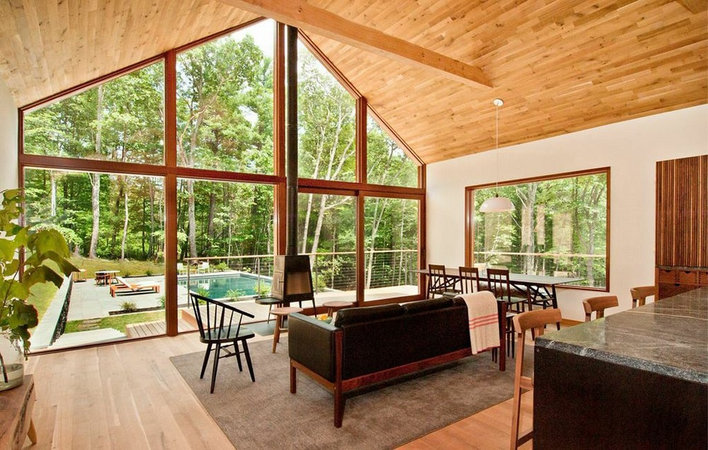 This is the living room with a large glass wall looking out onto the patio and backyard pool. This has a tall wooden cathedral ceiling that matches the tone of the hardwood flooring. Image courtesy of Toptenrealestatedeals.com.