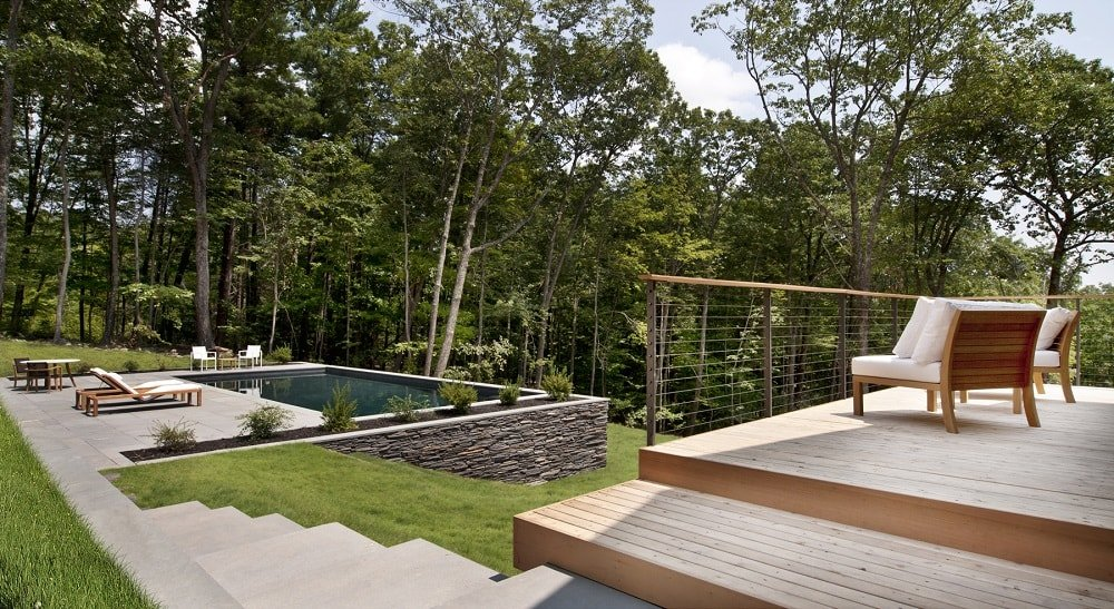 This is the patio with a wooden deck floor just outside the living room glass walls. This deck flooring leads to a set of stairs heading to the poolside area. Image courtesy of Toptenrealestatedeals.com.