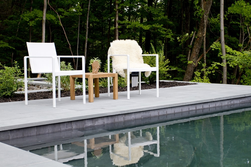 This is a closer look at the swimming pool that has concrete walkways fitted with a couple of outdoor armchairs with a wooden coffee table in the middle. Image courtesy of Toptenrealestatedeals.com.