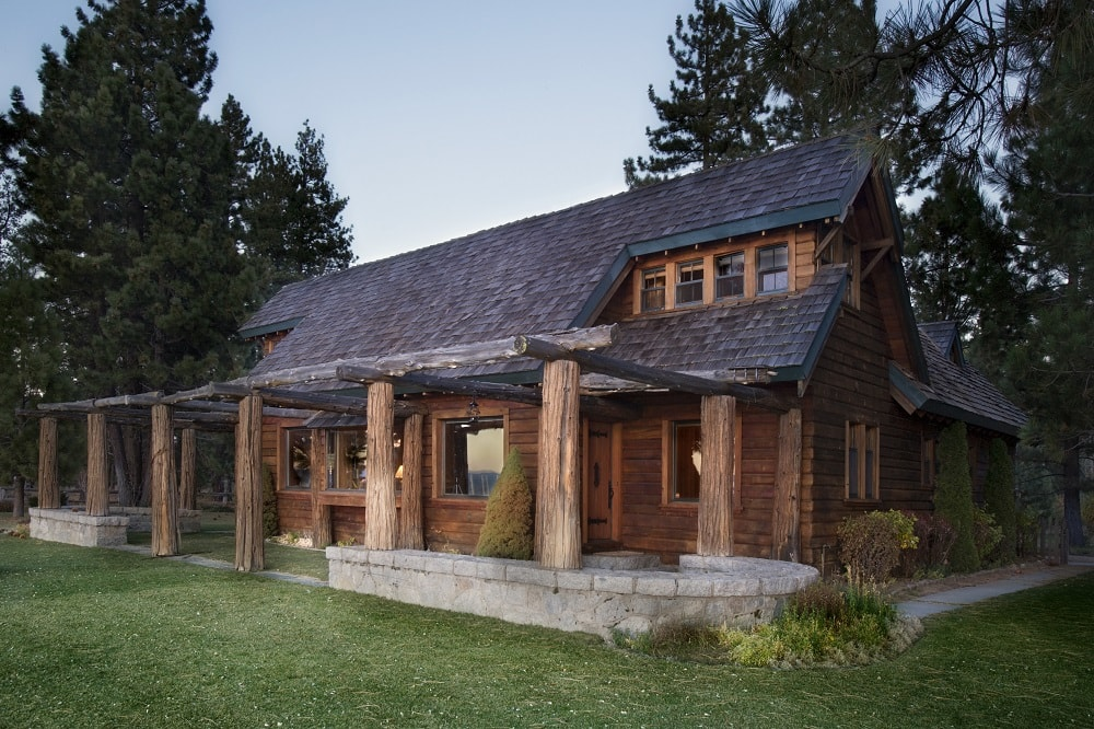 This is the front of the house facing the lake. You can see here that it has a small porch adorned with thick log pillars and a landscaping that has a grass lawn and tall trees in the background. Image courtesy of Toptenrealestatedeals.com.
