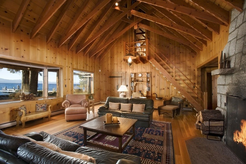This is the great room of the house showcasing the spacious living room. It has a tall wooden cathedral ceiling with exposed beams matching the wooden walls and hardwood flooring. It also has a large stone fireplace on the side. Image courtesy of Toptenrealestatedeals.com.