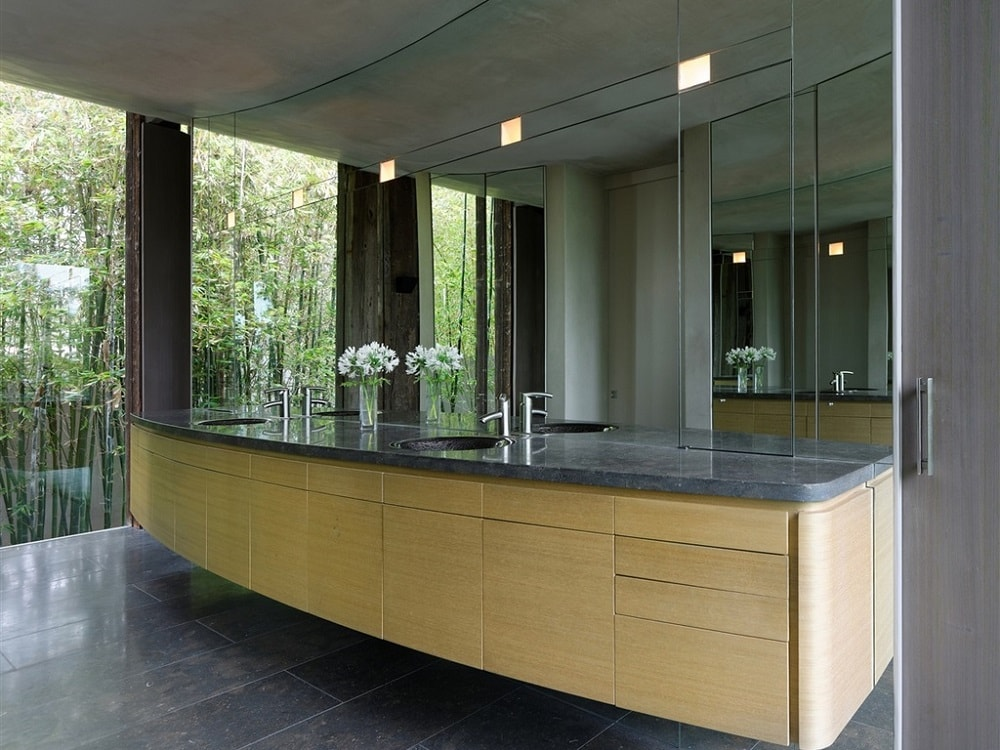 This is the two-sink floating modern vanity of the bathroom with a beige tone to its drawers topped with a large mirror. Image courtesy of Toptenrealestatedeals.com.