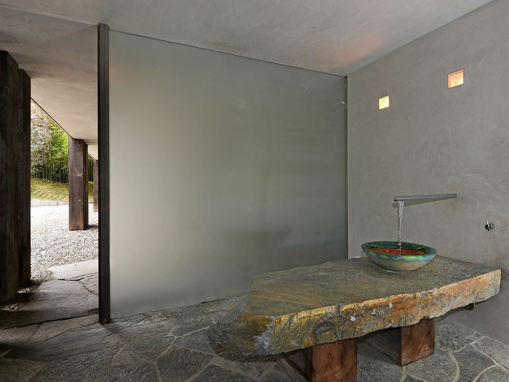 This bathroom has a rustic stone countertop that supports the bowl-sink next to a large frosted glass panel. Image courtesy of Toptenrealestatedeals.com.
