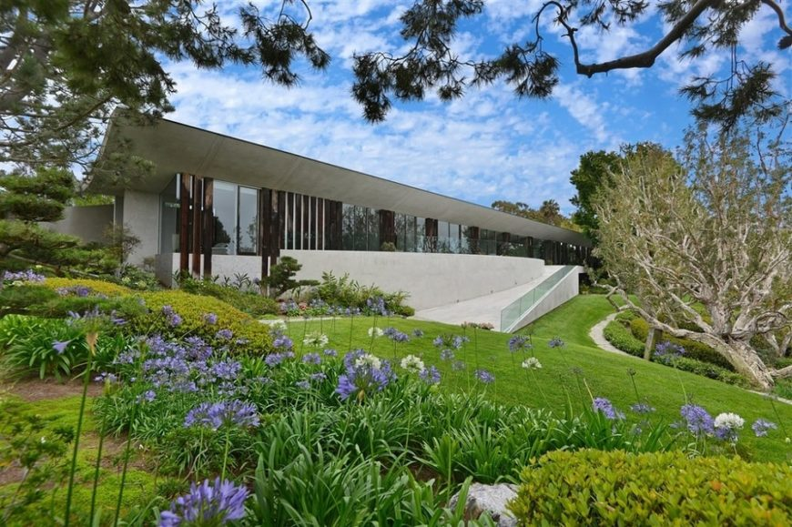 This is the front view of the contemporary-style home with lots of glass walls. This view gives us a taste of the juxtaposed modern elements with the natural landscape that surrounds the house. Image courtesy of Toptenrealestatedeals.com.